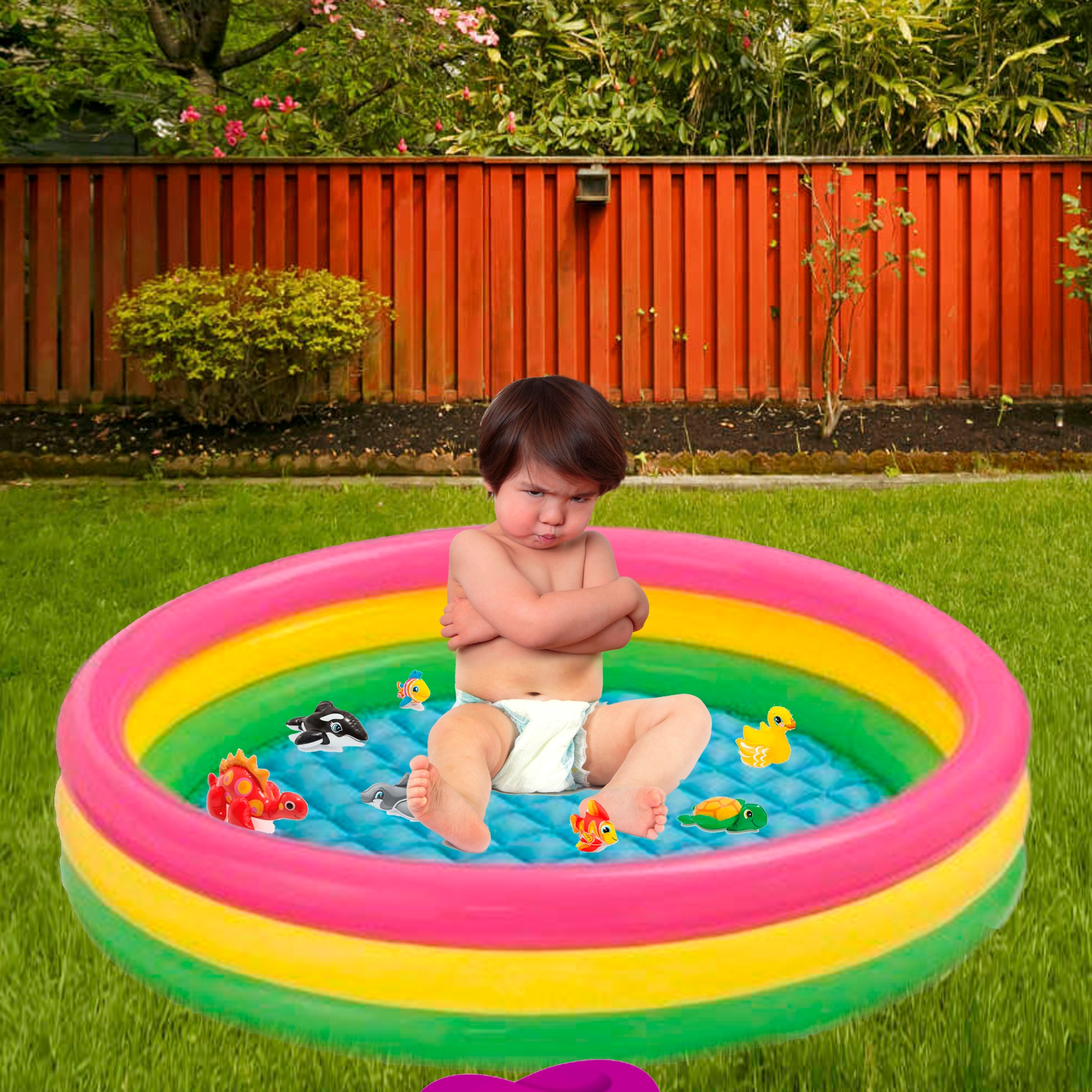 Angry baby sitting in the middle of a yard pool